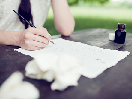 Womans hand writing love letter with ink outdoor